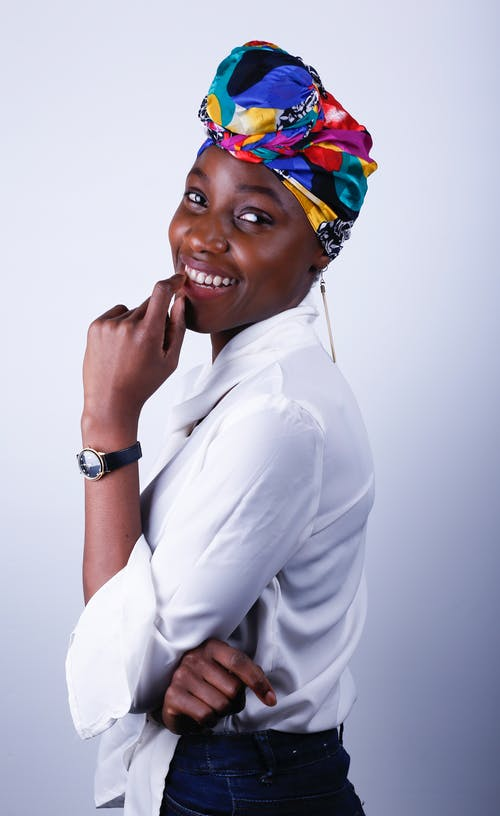 Side View Photo of Smiling Woman in White Dress Shirt, Black Jeans, and Multicolored Headscarf Posing In Front of White Background