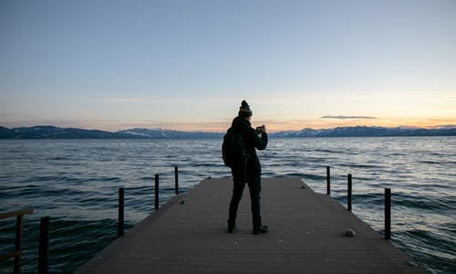 Man in Black Jacket Standing on Wooden Dock