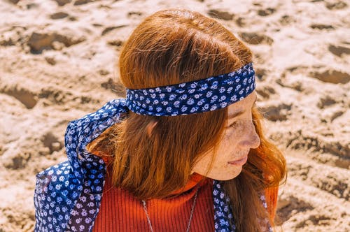 Photo of Woman With Freckles in Blue Floral Headscarf and Orange Top Looking Away While Sitting on Sand