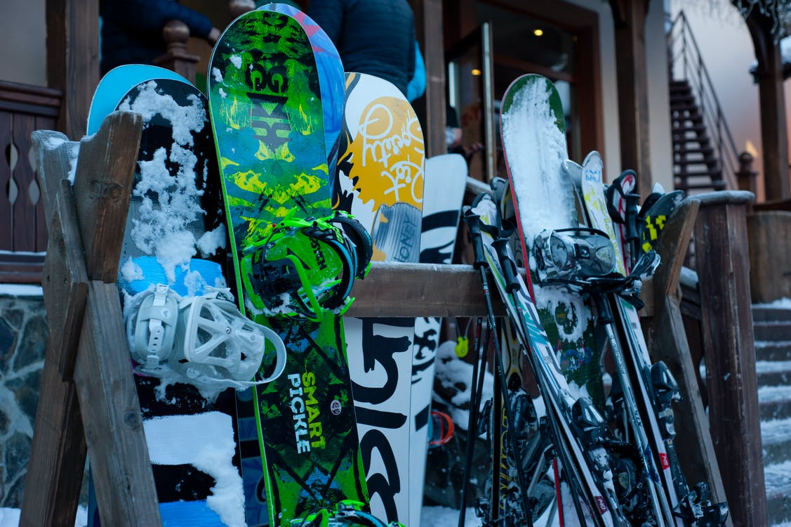 snowboards leaning on railing overlooking snowy mountain