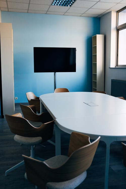Comfortable chairs and oval table in modern conference room with TV on daytime