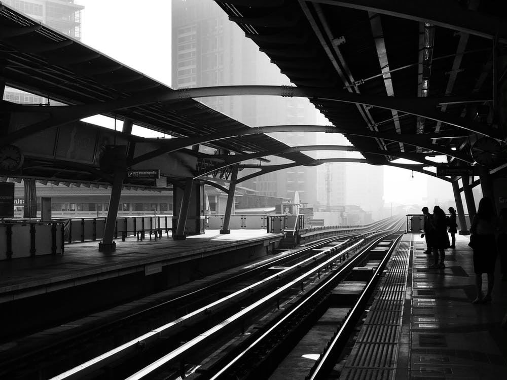Silhouettes of anonymous people standing on railway platform