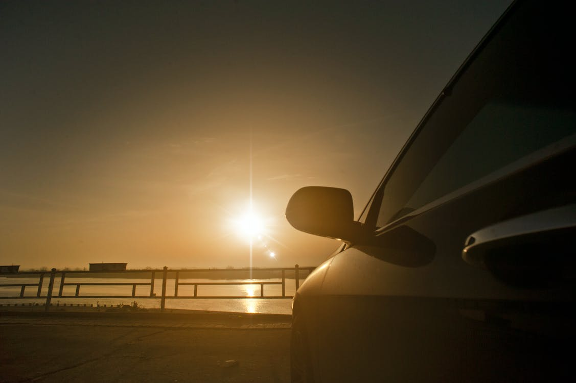 Photography of Car Parked in Front of Body of Water