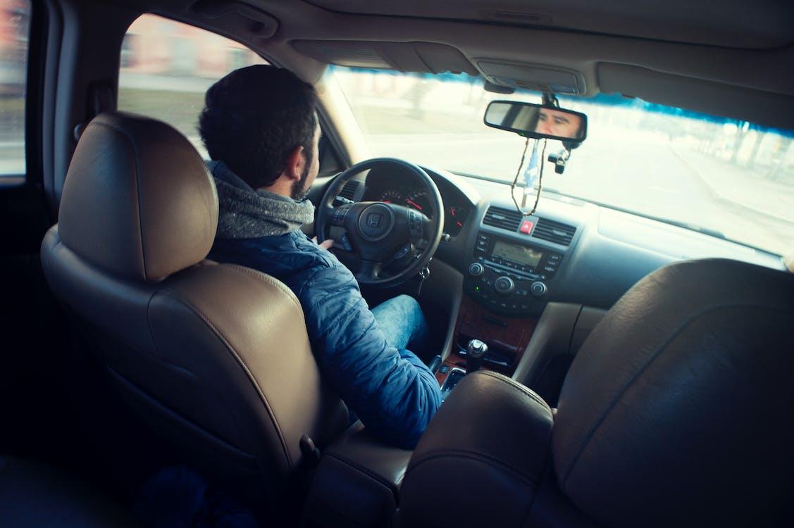 Man Wearing Blue Jacket Sitting Inside Car While Driving