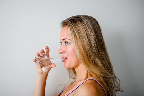 Photo of Woman Drinking from Plastic Cup