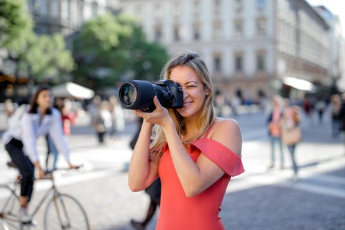 Woman Taking Photo Using Black Camera