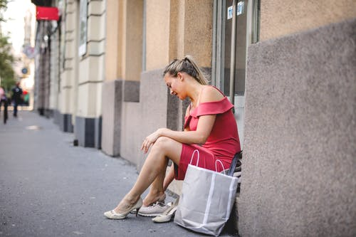 Photo of Woman in Pink Dress Wearing Her Shoe While Sitting on Doorstep