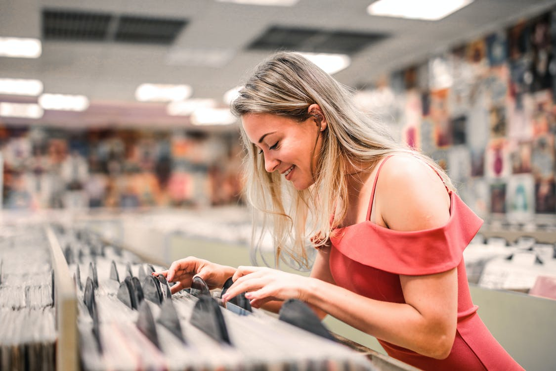 Selective Focus Photo of Smiling Woman in Pink Selecting Vinyl Records From a Music Store