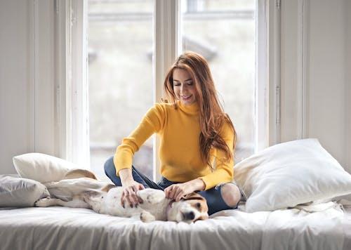 Foto De Uma Mulher Sorridente Com Um Suéter Amarelo De Gola Alta, Sentada Na Cama, Acariciando Seu Cachorro