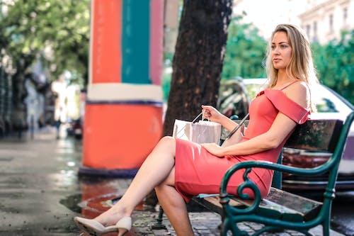 Woman Wearing Pink Dress While Sitting on Bench