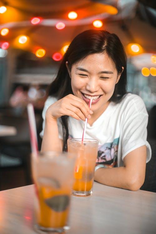 Веселая этническая женщина пьет вкусный напиток со льдом в кафе