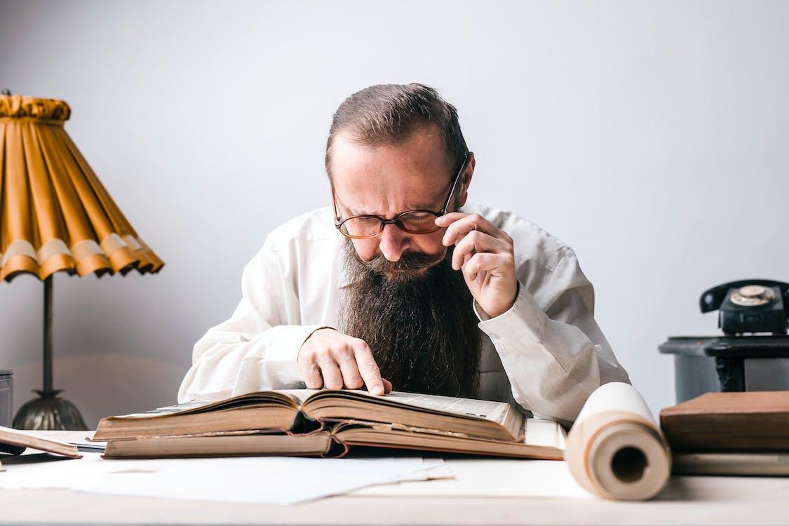 Man Wearing Black Framed Eyeglasses While Reading Book