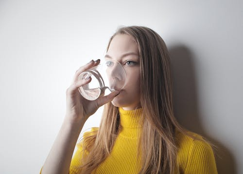 Woman Wearing Yellow Knit Sweater While Drinking Water