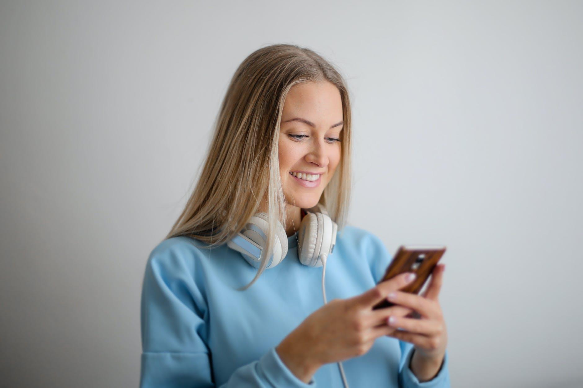Wanita memegang HP untuk transaksi BNI SMS Banking