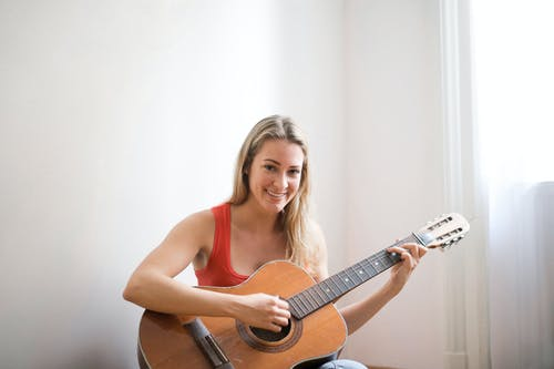 Woman in Red Tank Top Playing Brown Acoustic Guitar