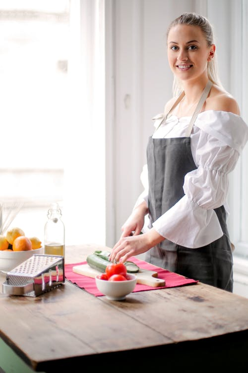 Woman Standing Near the Table While Wearing Apron