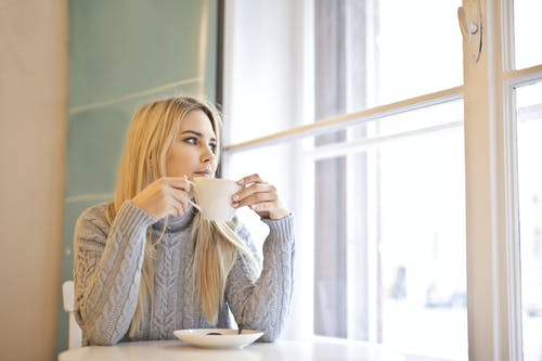 Woman in White Knit Sweater While Holding White Ceramic Mug