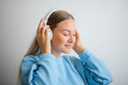 Portrait Photo of Woman in Blue Sweatshirt Wearing White Headphones Listening to Music