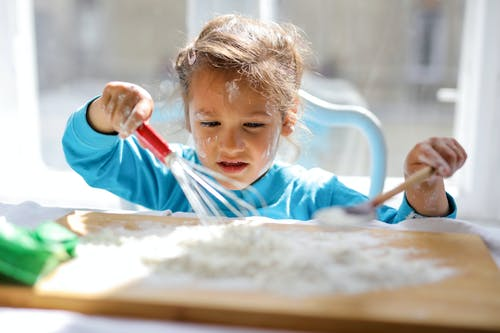 Girl Wearing Blue Top While Playing With Flour