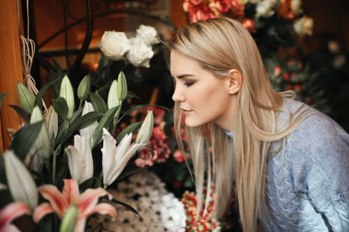 Woman Wearing Gray Sweater While Smelling the Flowers