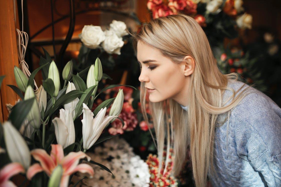 Mujer Vestida Con Suéter Gris Mientras Huele Las Flores