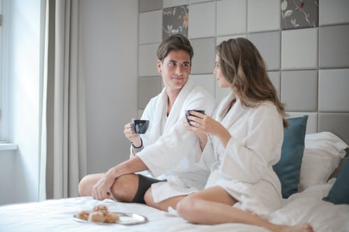 Woman in White Robe Sitting Beside Man on Bed