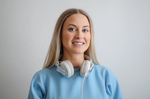 Woman in Blue Long Sleeve Shirt Wearing White Headphones