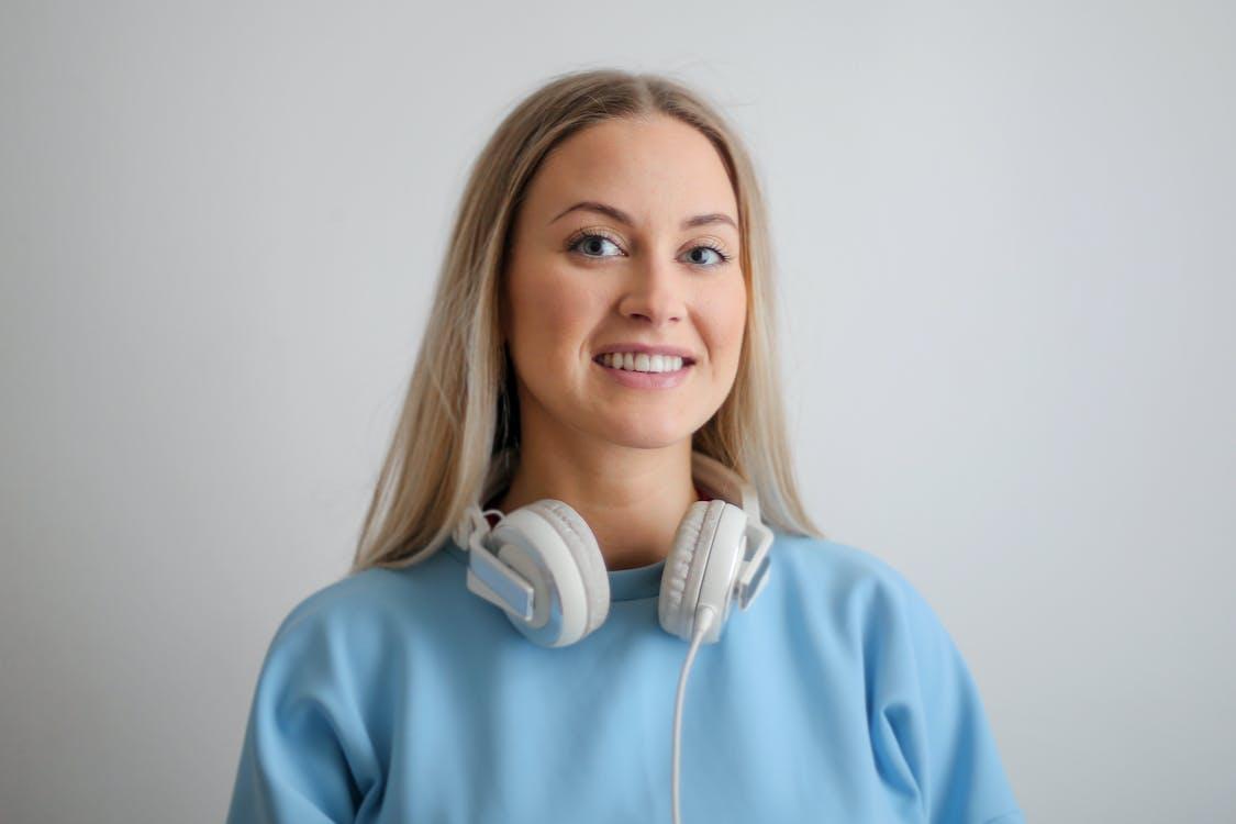 Woman in Blue Long Sleeve Shirt Wearing White Headphones