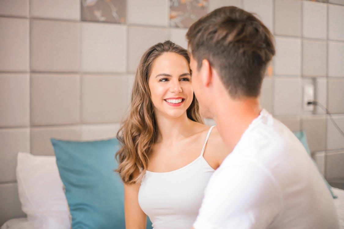 Woman in White Spaghetti Strap Top Smiling Beside Man in White Dress Shirt