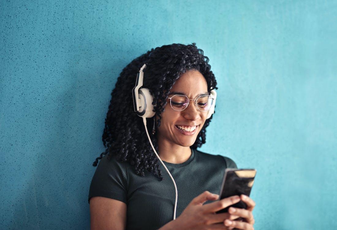 Woman in Black Crew Neck T-shirt Wearing White Headphones