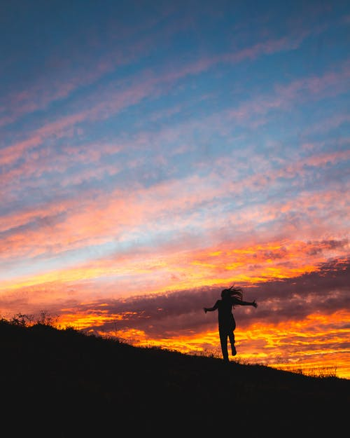 Silhouette Photo of Person Standing on Hill during Sunset