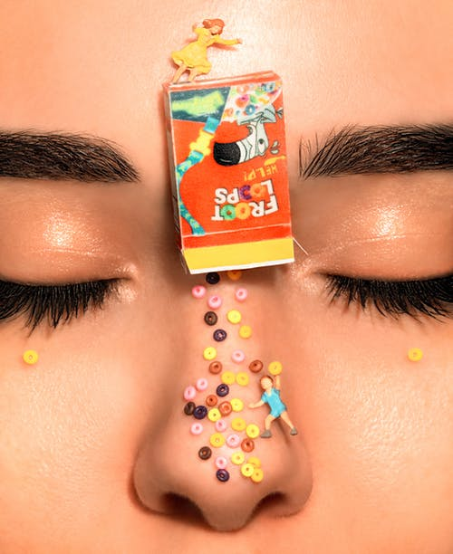 Close-Up Photo of Person With Froot Loops on Face