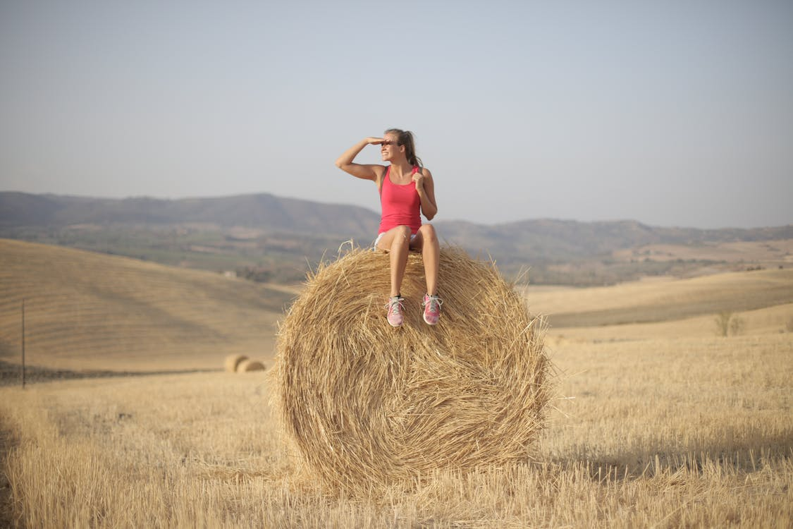Woman in Pink Tank Top Sitting on Hay Roll