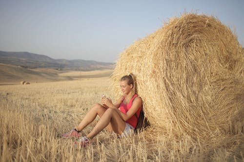 Woman in Pink Tank Top Leaning on Brown Hay Roll