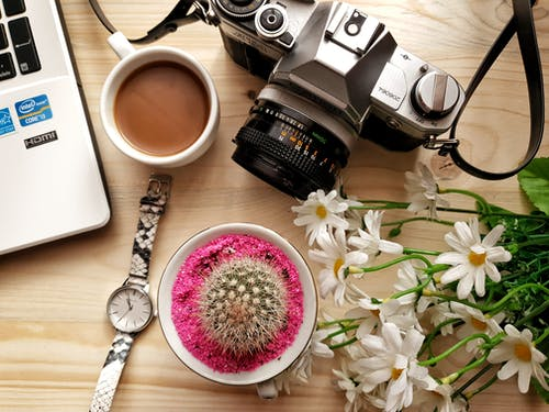 Gray Dslr Camera Beside Flowers and Wrist Watch Near Coffee