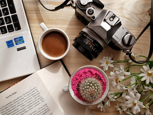 Gray Dslr Camera Beside White Ceramic Mug With Brown Liquid