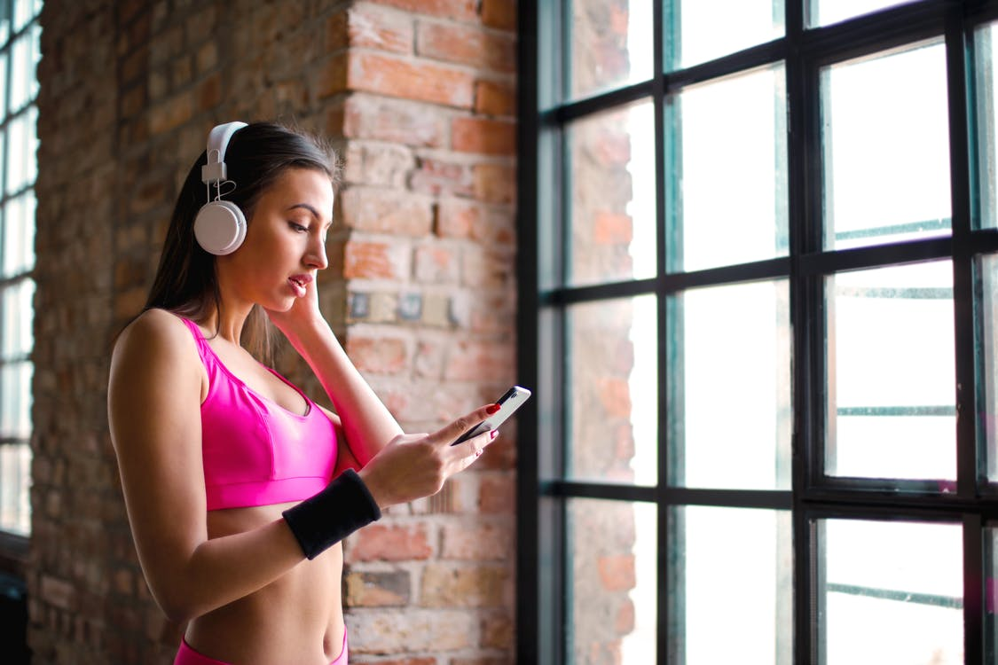 Woman in Pink Sports Bra While Holding Smartphone