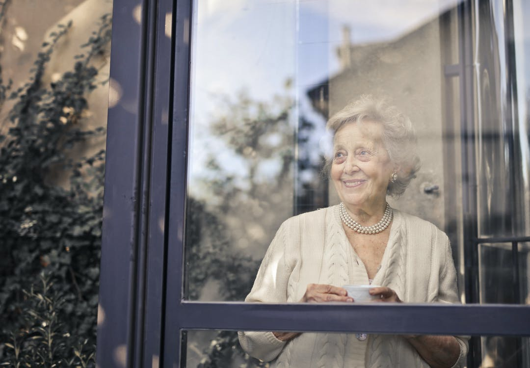 Woman in White Dress Shirt Standing in Front of Glass Window