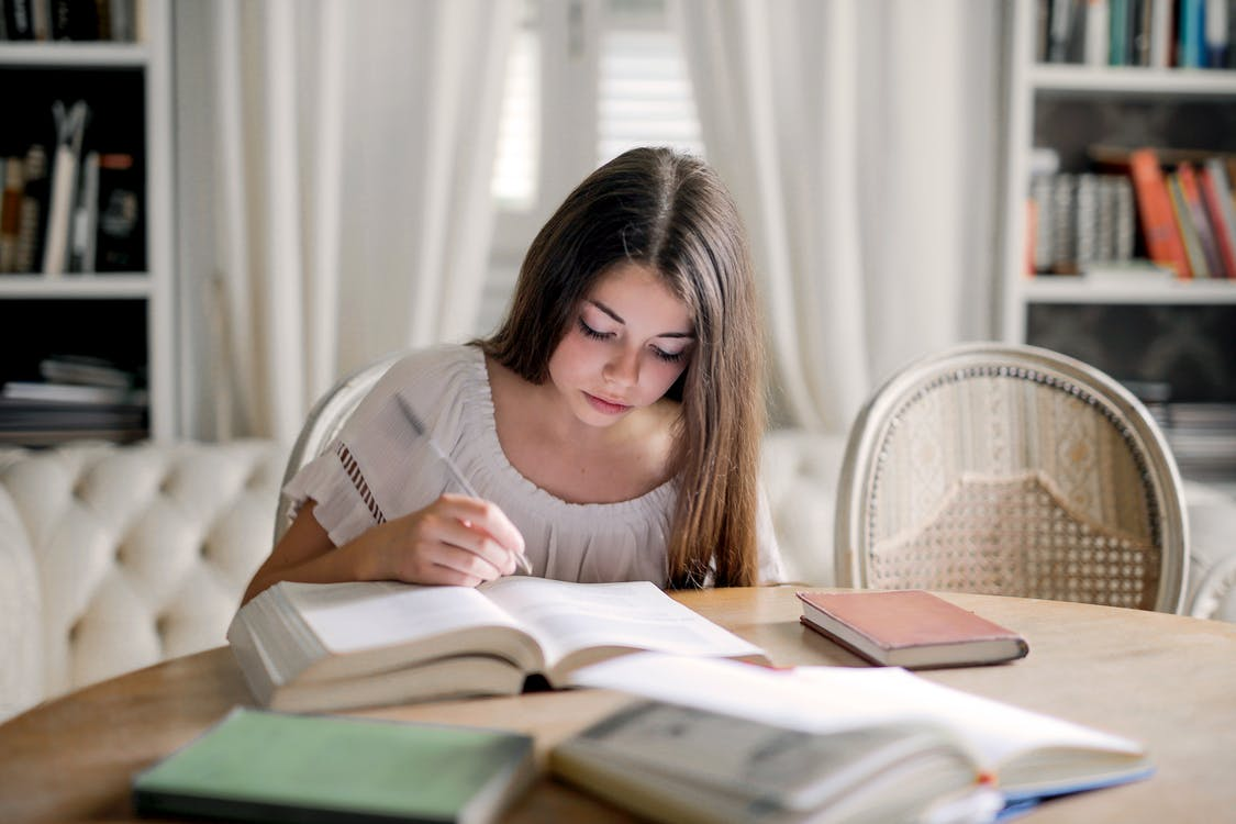 Woman in White Long Sleeve Shirt While Reading Book