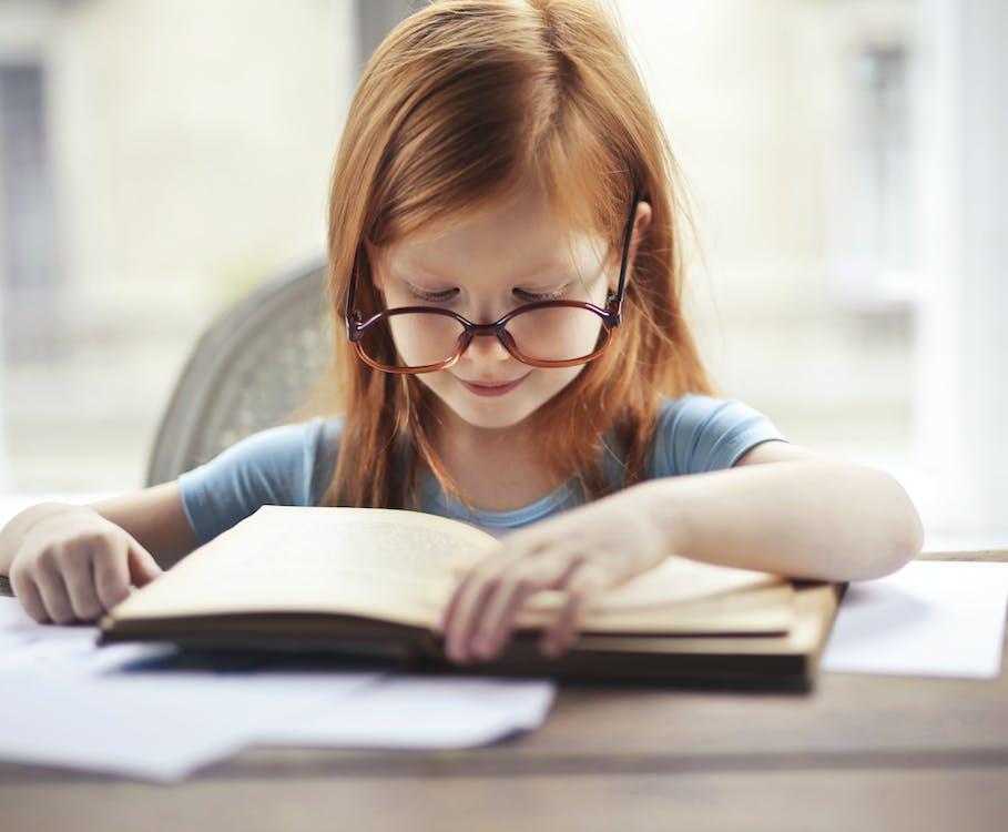 Girl in Blue Long Sleeve Shirt Reading Book