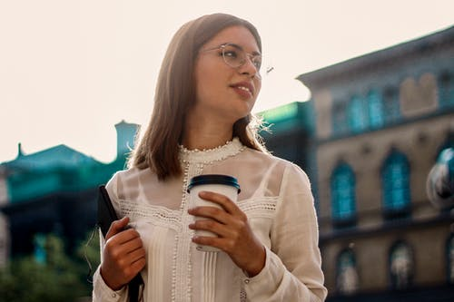 Woman in White Long Sleeve Shirt While Holding Cup