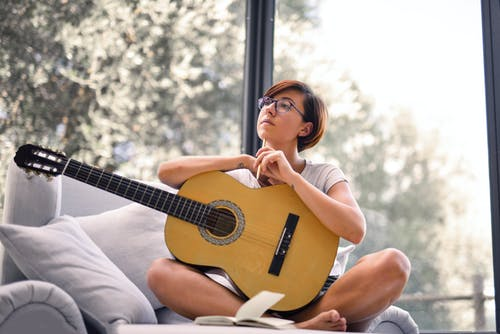 Woman in White Tank Top While Holding Acoustic Guitar