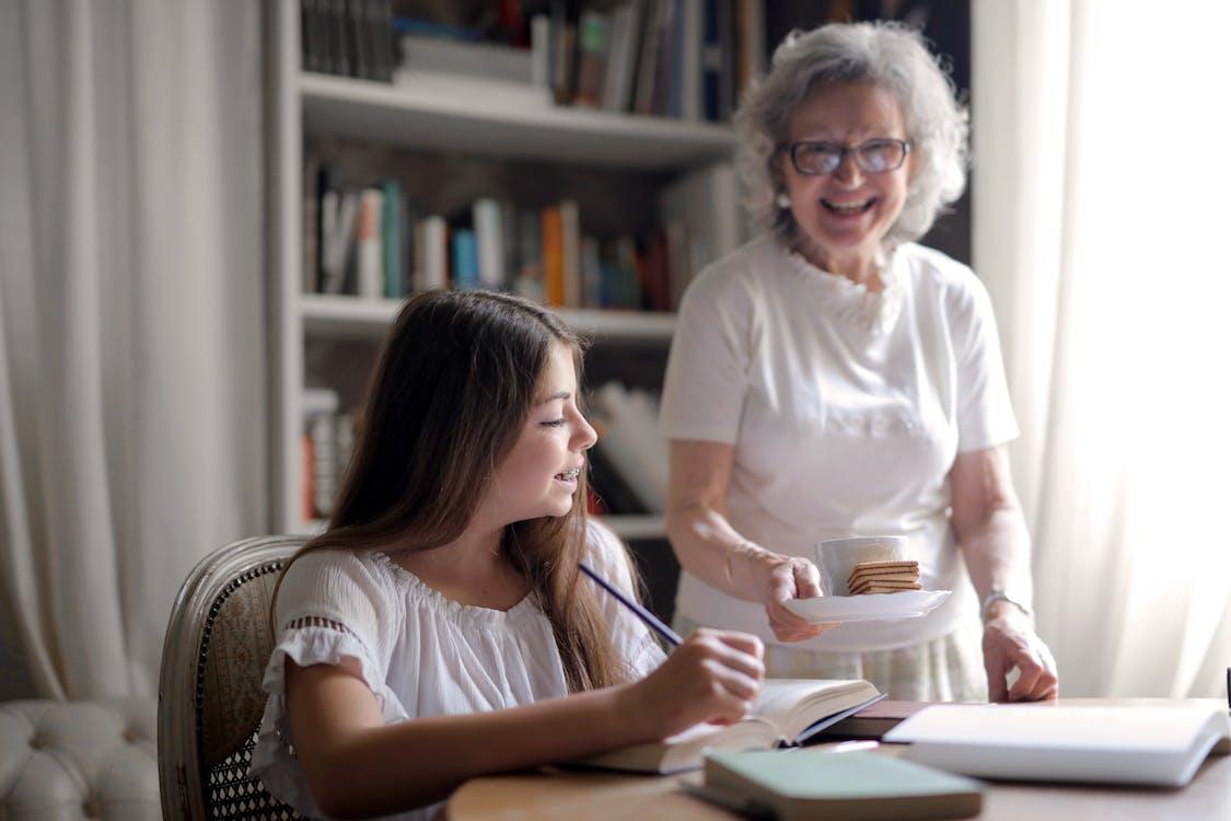 Heureuse Femme âgée Donnant Des Biscuits Et Une Tasse De Boisson Chaude à Petite Fille Heureuse De Faire Ses Devoirs à La Maison