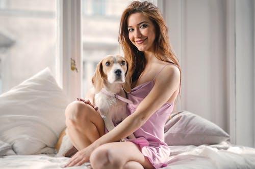 Frau Im Rosa Kleid, Das Auf Bett Mit Weißem Und Braunem Kurzbeschichtetem Hund Sitzt