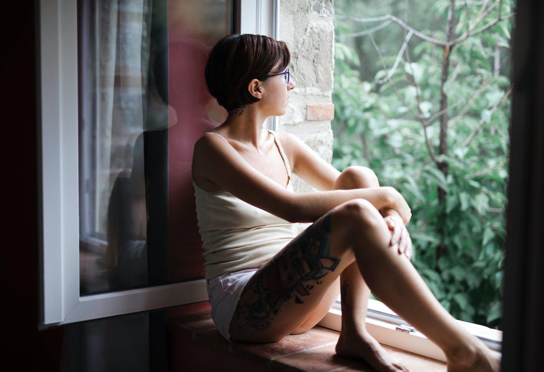 Woman in White Tank Top Sitting on Window Pane