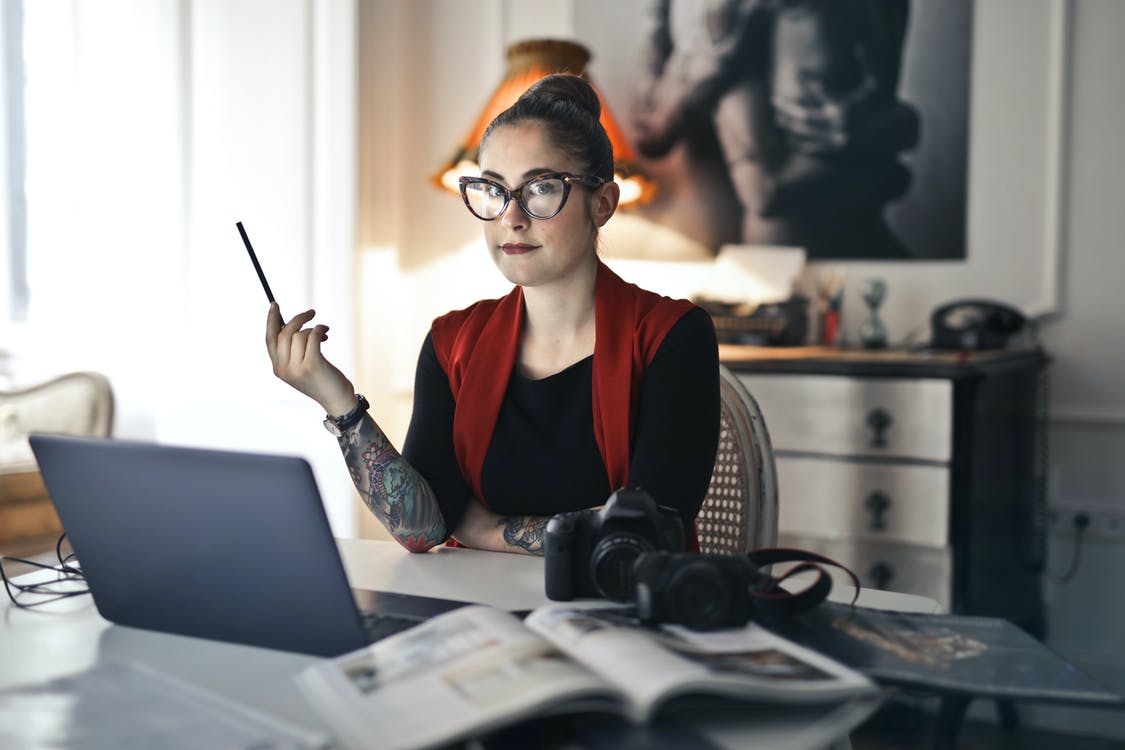 Informal adult woman using laptop for working with photo project