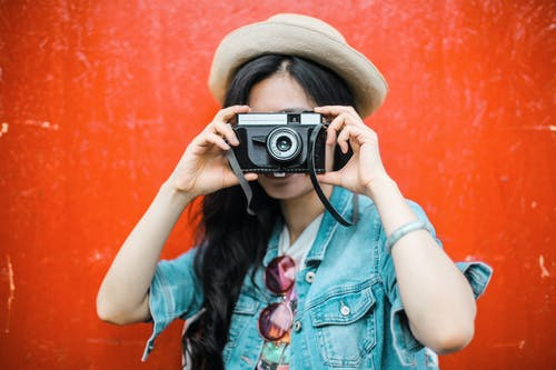 Woman in Blue Denim Jacket Holding Black Camera