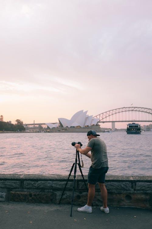 Man Setting Up Black Dslr Camera on Tripod Near the River