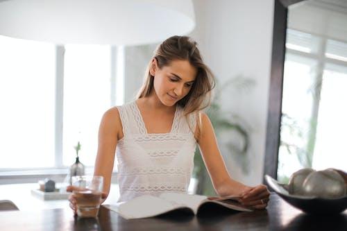 Frau Im Weißen ärmellosen Oberteil Beim Lesen