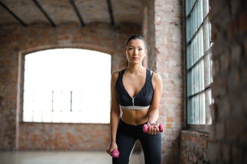 Женщина в черном спортивном бюстгальтере и черных леггинсах